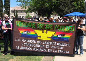 Queer protesters display a sign in a park